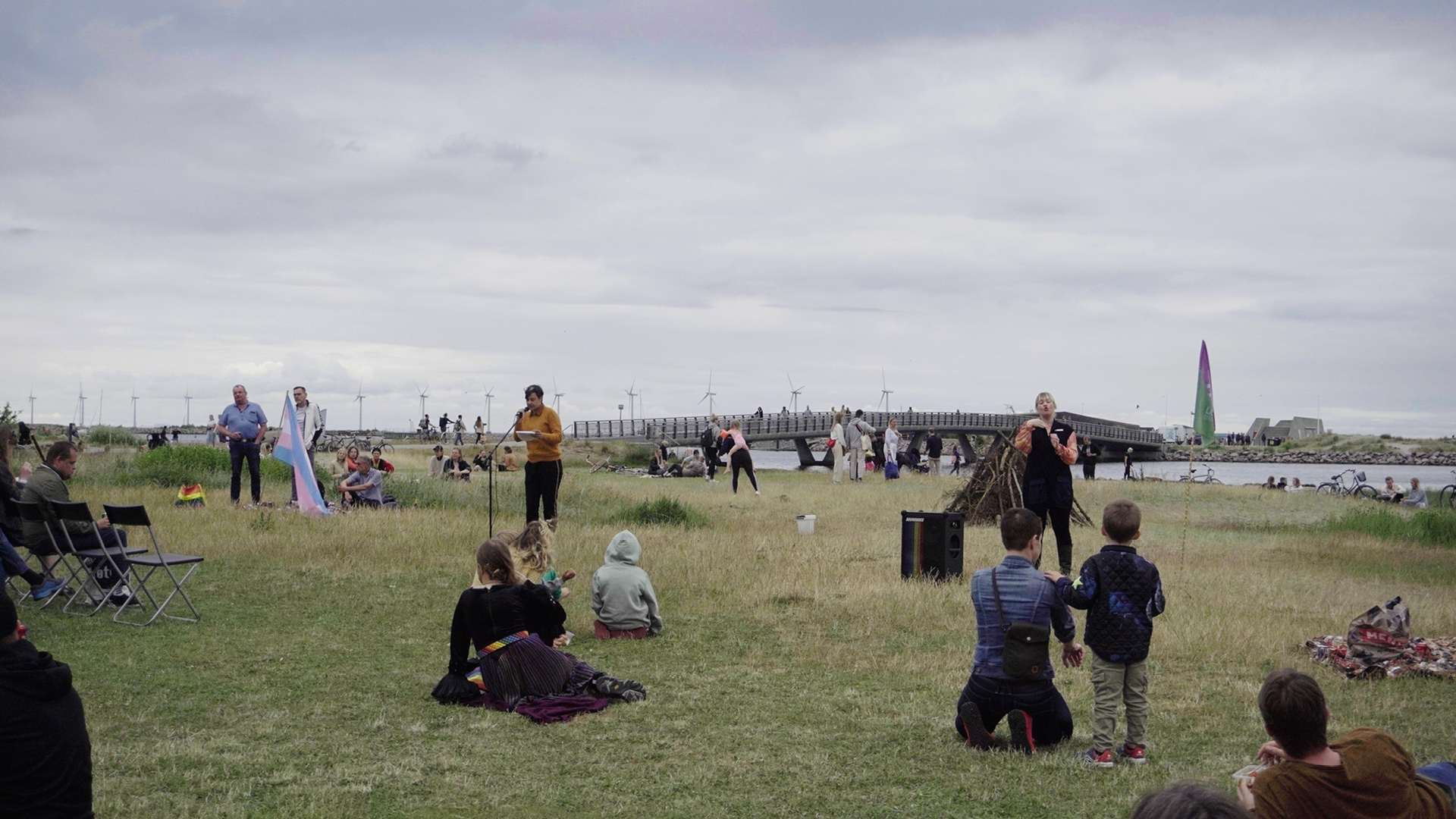 Susanne Branner Jesperne holder tale på græsplane foran publik og ved siden af en tegnsprogstolk.