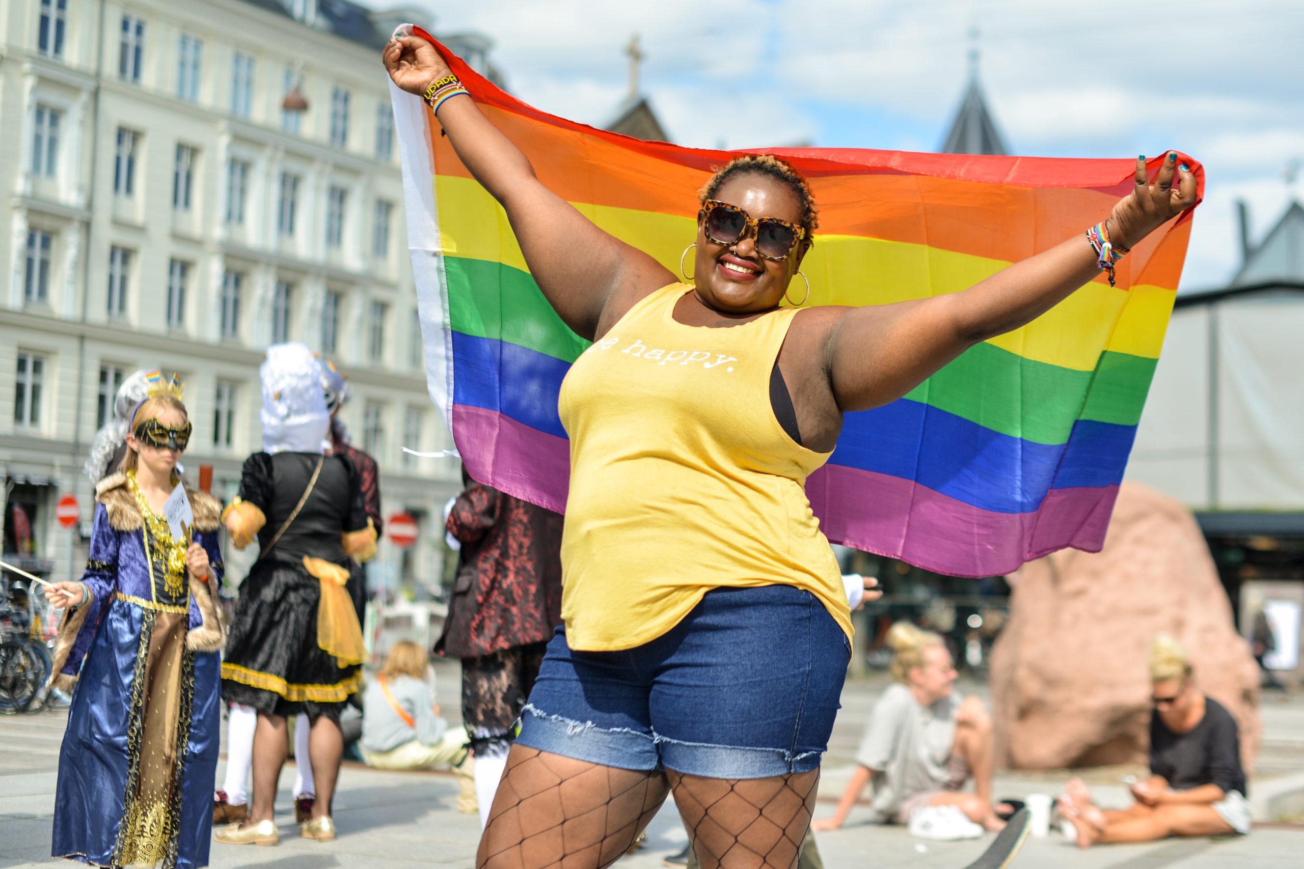 Pridedeltager holder regnbueflag højt