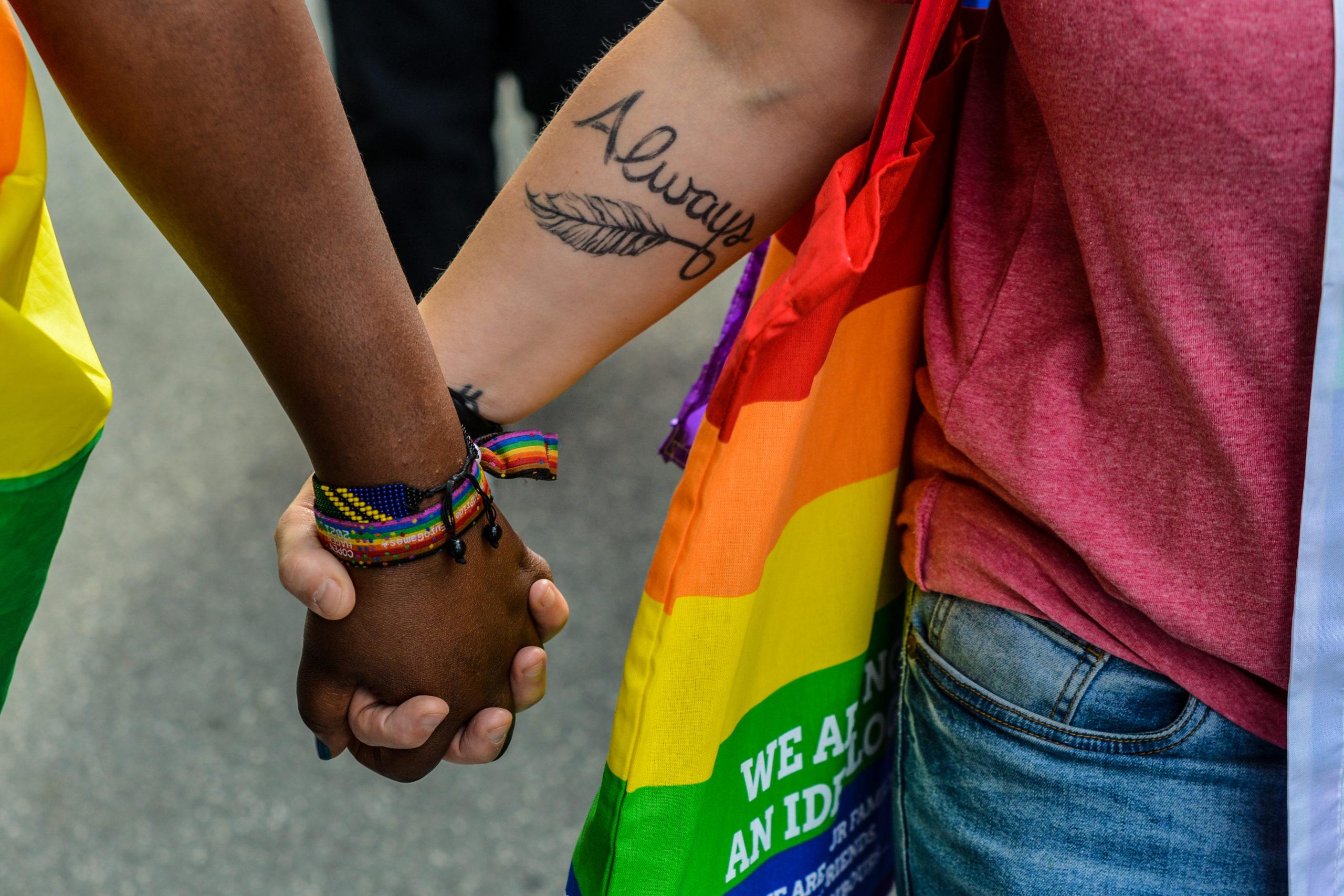 To hænder i forskellig hudfarve holder hånd under prideoptog