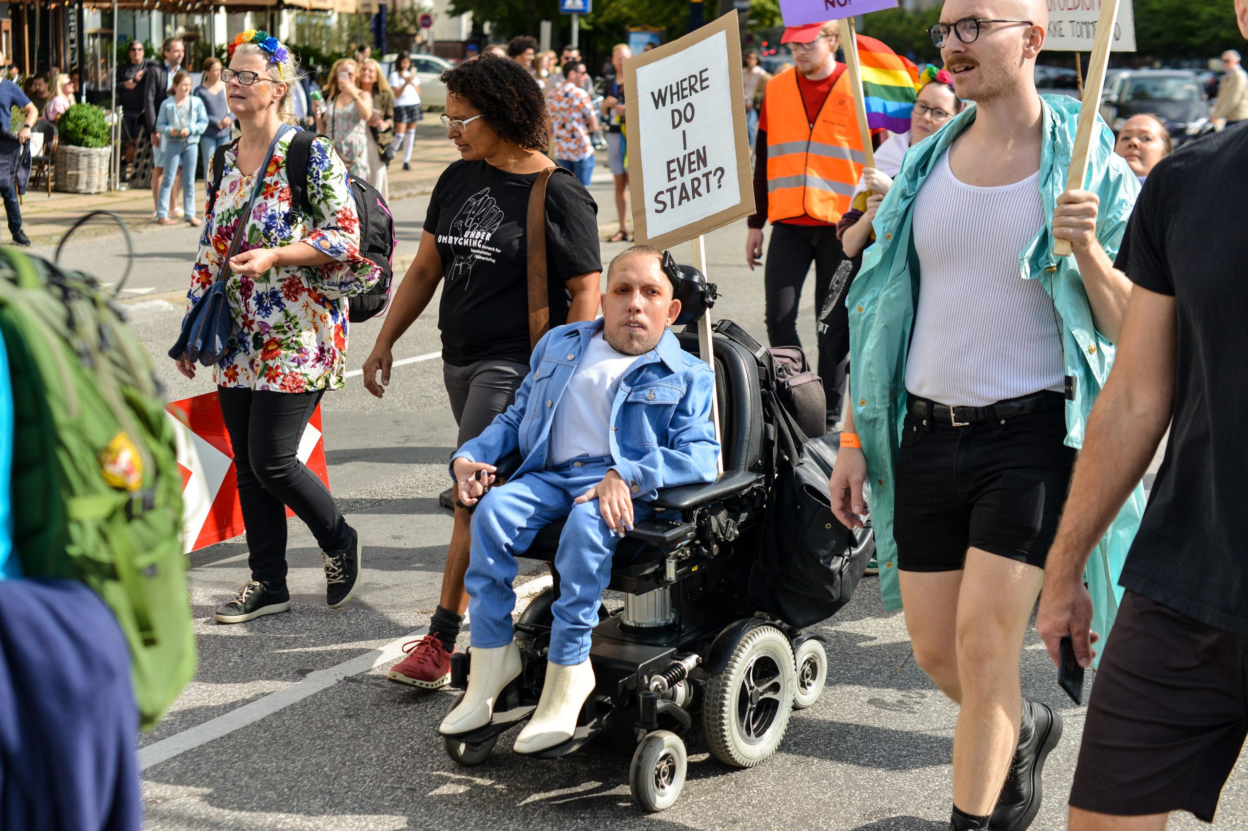 """Pridedeltager i kørestol med skilt, hvor på der står skrevet """"Where do I even start?"""""""